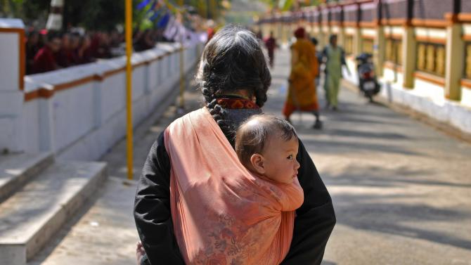 A Tibetan woman carries a child as she walks to attend the Jangchup Lamrim teachings conducted by the Dalai Lama at Mundgod
