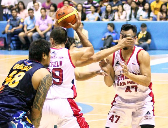Ryan Arana (behind) slaps the face of Mark Caguioa while Rudy Hatfield tries to hand off the ball. (PBA Images)