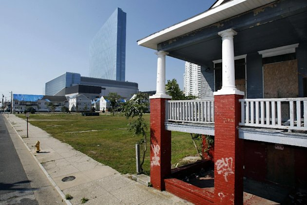 This July 17, 2013 photo shows buildings with blue tarpaulins on roofs and boarded windows near the year-old Revel Casino-Hotel in Atlantic City, N.J. Some criticize the way the state Casino Reinvestment Development Authority, which in 2011 was given the authority to run the city's tourism district, has handled plans to redevelop the neighborhood, which sits in the shadows of Revel. Low-income and middle-class residents accuse developers and officials of treating their homes like houses and hotels in Monopoly, the board game inspired by Atlantic City real estate. (AP Photo/Mel Evans)