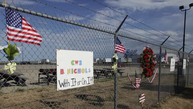 A memorial for Army Chief Warrant Officer 2 Bryan Nichols hangs on the fence outside the Army Reserve base of Bravo Company, 7th Battalion, 158th Aviation Regiment in Gardner, Kan., Monday, Aug. 8, 2011. Nichols was one of three in the unit that died in the U.S. helicopter crash in Afghanistan. (AP Photo/Orlin Wagner)
