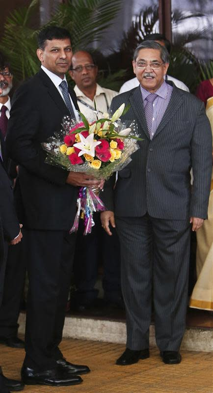 Newly appointed governor of RBI Rajan receives a bouquet from deputy governor Chakrabarty in Mumbai