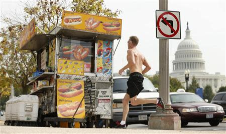 A jogger passes a street food vendor next to the U.S. Capitol in Washington