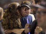 Firefighter Brendan McDonough embraces a mourner near the end of a candlelight vigil in Prescott, Ariz. on Tuesday, July 2, 2013. McDonough was the sole survivor of the 20-man Granite Mountain Hotshot Crew after an out-of-control blaze killed the 19 on Sunday near Yarnell, Ariz. (AP Photo/Julie Jacobson)