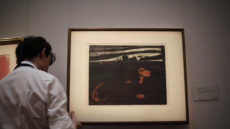 "An employee of the Sotheby's auction house rehangs Edvard Munch's ""Melancholy III"" a woodcut printed in blue, ochre, light-gey and black from 1902, at their premises in London, Thursday, March 13, 2014. The screenprint is estimated to fetch between 120,000 to 180,000 pounds ($200,227 to $300,341 or 143,602 to 215,403 euro) in a ""Prints and Multiples"" auction on March 18. (AP Photo/Matt Dunham)"