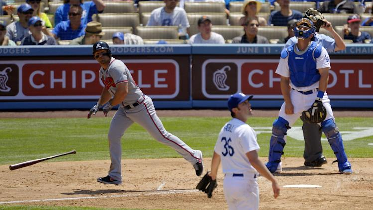 Atlanta Braves' Dan Uggla, left, hits a three-run home run as Los Angeles Dodgers starting pitcher Matt Magill, center, and catcher Tim Federowicz look on during the third inning of their baseball game, Sunday, June 9, 2013, in Los Angeles. (AP Photo/Mark J. Terrill)