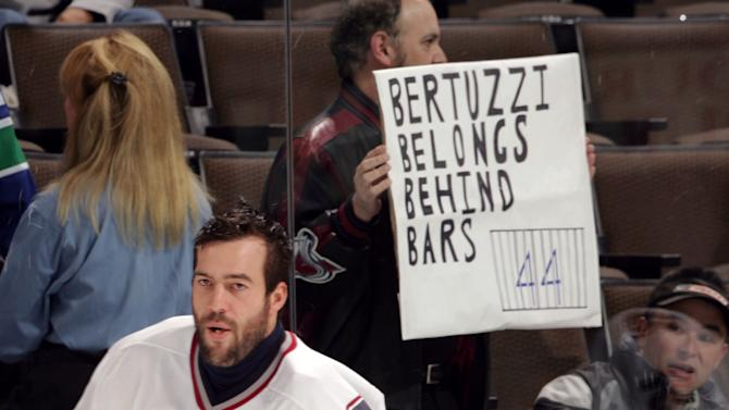 """Vancouver Canucks right winger Todd Bertuzzi, front, skates past an unidentified fan holding a sign that reads """"Bertuzzi Belongs Behind Bars,"""" during the team's skate prior to playing the Colorado Avalanche, Saturday, Oct. 29, 2005, in Denver. Bertuzzi, who hit former Colorado forward Steve Moore from behind and broke his neck in a game March 8, 2004, in Vancouver, was making his second appearance in Denver since the on-ice attack"""