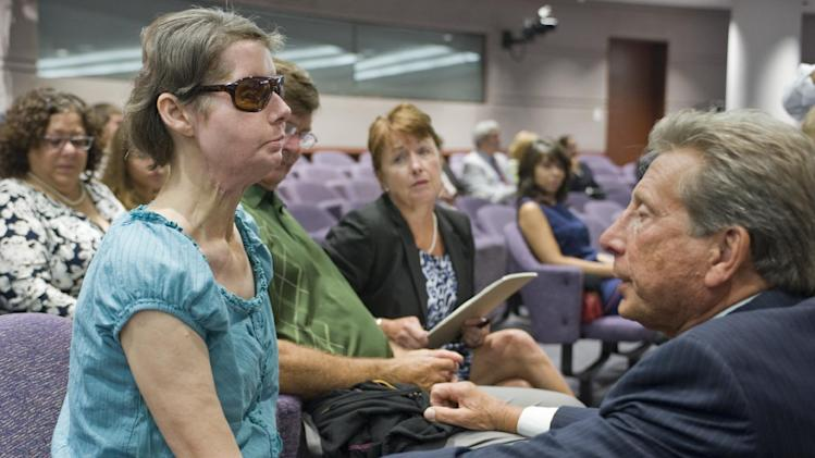 Charla Nash, left, talks with attorney Charles J. Willinger, Jr., right, before a hearing at the Legislative Office Building in Hartford, Conn., Friday, Aug. 10, 2012.  Nash who was mauled in a 2009 chimpanzee attack is attending a hearing to determine whether she may sue the state for $150 million in claimed damages. (AP Photo/Jessica Hill)