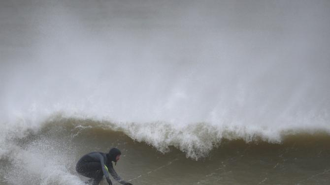 A surfer rides a wave as the wind wips spray off the wave off the coast at Newhaven, southern England