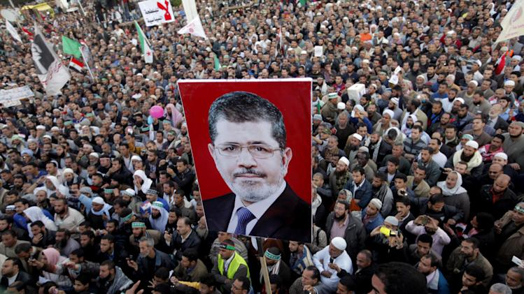 Thousands of Egyptian protesters shout slogans supporting Islamist President Mohammed Morsi, his poster at center, during a rally outside Cairo University in Cairo, Egypt, Friday, Feb. 15, 2013. Several thousand mostly hard-line Islamists protested in Cairo on Friday against a recent wave of violent anti-government protests, while liberal activists staged a smaller demonstration across town to call for accountability and justice from the country's leaders.(AP Photo/Amr Nabil)