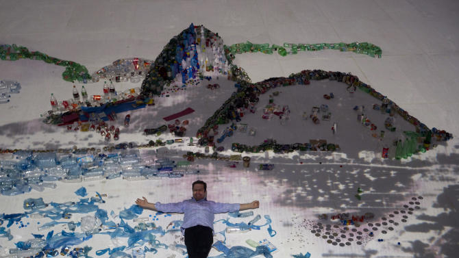 "Brazilian artist Vik Muniz poses for a photo as he lies on his ""Landscape"" project that uses waste to recreate the image of Guanabara Bay in Rio de Janeiro, Brazil, Saturday, June 16, 2012. Muniz's project recreates city landmarks with recyclable materials donated by the public, who will be able to take their waste to the installation's tent between June 15 and 22, on the sidelines of the UN Conference on Sustainable Development, or Rio+20. (AP Photo/Silvia Izquierdo)"