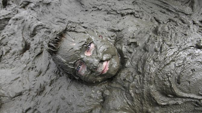Zach Miller, 10, of Livonia lies in mud in Westland, Mich., Tuesday, July 9, 2013. Hundreds of kids enjoyed the annual Mud Day event in a 7-by-150-foot mud pit. (AP Photo/Paul Sancya)