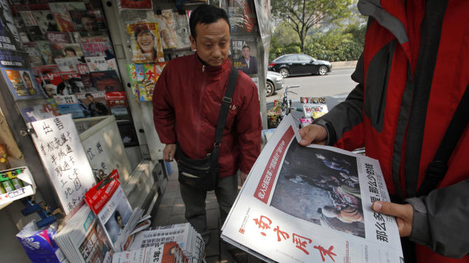 A man buys a latest edition of Southern Weekly newspaper at a newsstand near the headquarters of the newspaper in Guangzhou, Guangdong province, China Thursday, Jan. 10, 2013. The influential weekly newspaper whose staff rebelled to protest heavy-handed censorship by China's government officials published as normal Thursday after a compromise that called for relaxing some intrusive controls but left lingering ill-will among some reporters and editors. (AP Photo/ Vincent Yu)