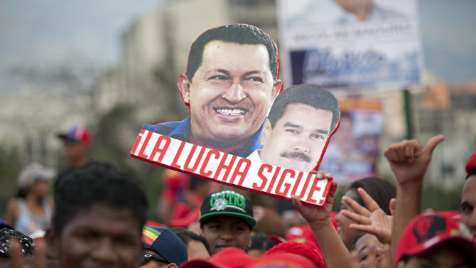 "A supporter holds up a sign that reads in Spanish ""The fight continues"" and shows late President Hugo Chavez, left, and current presidential candidate Nicolas Maduro, before the closing campaign rally for Maduro in Caracas, Venezuela, Thursday, April 11, 2013. Maduro, Chavez's hand-picked successor, is running for president against opposition candidate Henrique Capriles on April 14. (AP Photo/Ramon Espinosa)"