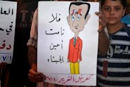 "A handout image released by the Syrian opposition's Shaam News Network on July 2, shows a Syrian protester holding a poster depicting Bashar al-Assad with the Arabic writing ""May the eyes of cowards never rest"" during an anti-regime demonstration in Kfar Nubul. AFP cannot independently verify this image"