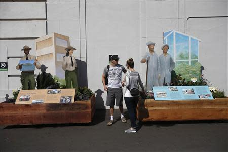A couple stand between two National Park Service display at Pier 33 in San Francisco, California