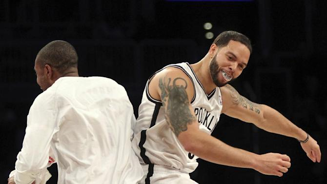 Brooklyn Nets' Deron Williams, right, celebrates with C.J. Watson after scoring a 3-pointer during the first half of NBA basketball game against the Washington Wizards, Friday, March 8, 2013, in New York. Williams set the NBA record with nine 3-pointers in a half in the first half of the game. (AP Photo/Mary Altaffer)