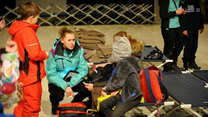 A representative of the Crystal tour operator (2nd L) talks with stranded British holiday makers waiting in a civic hall due to roads being blocked by heavy snowfall in Albertville, France, on December 28, 2014