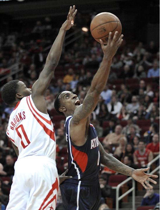Atlanta Hawks' Jeff Teague, right, goes to the basket as Houston Rockets' Aaron Brooks (0) defends during the first half of an NBA basketball game Wednesday, Nov. 27, 2013, in Houston