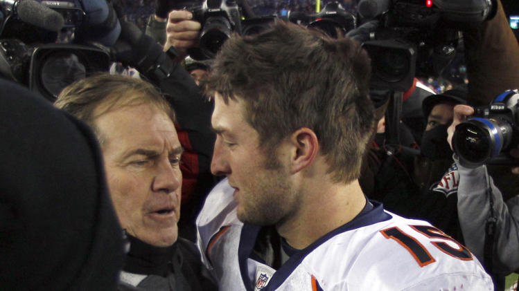 Denver Broncos quarterback Tim Tebow, right, hugs New England Patriots head coach Bill Belichick following an NFL divisional playoff football game Saturday, Jan. 14, 2012, in Foxborough, Mass. The Patriots defeated the Broncos 45-10. (AP Photo/Charles Krupa)