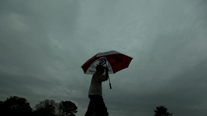 A spectator walks off the course as a weather warning delays the first round of the U.S. Open golf tournament at Merion Golf Club, Thursday, June 13, 2013, in Ardmore, Pa. (AP Photo/Charlie Riedel)