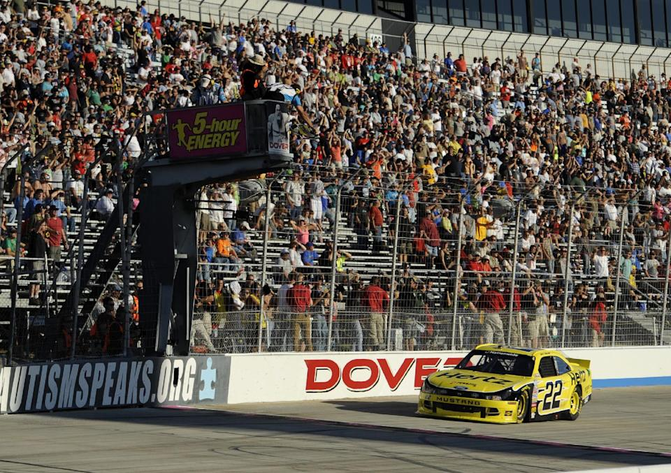 Joey Logano takes the checkered flag to win the NASCAR Nationwide Series auto race, Saturday, Sept. 28, 2013, at Dover International Speedway in Dover, Del. (AP Photo/Nick Wass)