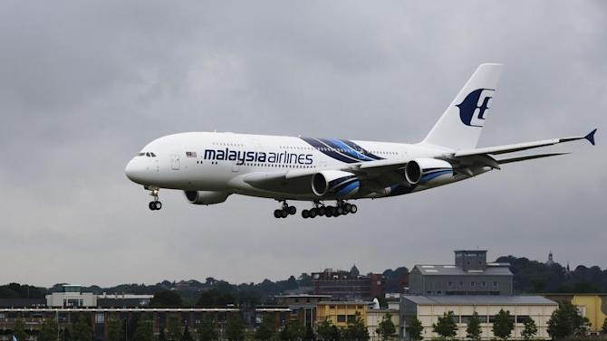 An Airbus A380, owned by Malaysia Airlines, lands ahead of the Farnborough Airshow 2012 in southern England