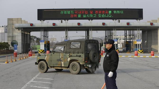 A South Korean military vehicle passes by gates leading to the North Korean city of Kaesong at the customs, immigration and quarantine office near the border village of Panmunjom, which has separated the two Koreas since the Korean War, in Paju, north of Seoul, South Korea, Monday, April 8, 2013. A top South Korean national security official said Sunday that North Korea may be setting the stage for a missile test or another provocative act with its warning that it soon will be unable to guarantee diplomats' safety in Pyongyang. But he added that the North's clearest objective is to extract concessions from Washington and Seoul. (AP Photo/Lee Jin-man)