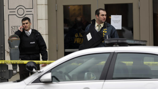 Police investigate outside the scene of a shooting Tuesday, Jan. 15, 2013, in St. Louis. Police say a gunman walked into the Stevens Institute of Business and Arts business school in downtown St. Louis and shot an administrator in the chest before shooting himself. (AP Photo/Jeff Roberson)