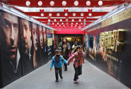 In this Feb. 7, 2013 photo, movie goers head to a popular theater complex as the Chinese New Year nears in Taipei, Taiwan. Tens of millions of film fanatics are entering theaters around Asia during the long Lunar New Year holiday, but Hollywood can't count on them to boost the box office for its mostly serious Oscar nominees. Even with the Academy Awards buzz at a peak barely two weeks before the ceremony, patrons are opting for lighter fare. (AP Photo/Wally Santana)