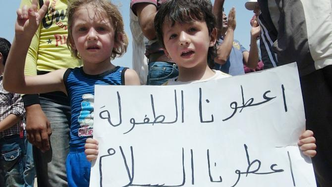 "In this citizen journalism image provided by the Local Coordination Committees in Syria and accessed on Friday, June 15, 2012, Syrian children hold a poster with Arabic that reads, ""give us a childhood give us peace, and that's all,"" during a demonstration in Idlib, north Syria. (AP Photo/Local Coordination Committees in Syria) THE ASSOCIATED PRESS IS UNABLE TO INDEPENDENTLY VERIFY THE AUTHENTICITY, CONTENT, LOCATION OR DATE OF THIS HANDOUT PHOTO"