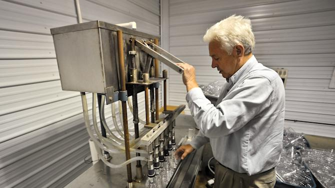 ADVANCE FOR SUNDAY JUNE 3 AND THEREAFTER In this Thursday May 17, 2012 photo West Virginia State Senator Walt Helmick, works his bottling machine  at his Pocahontas County W. Va., bottling plant and farm. (AP Photo/Charleston Daily Mail, Bob Wojcieszak)
