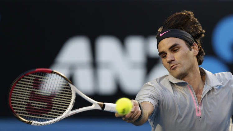 Switzerland's Roger Federer hits a forehand return to Australia's Bernard Tomic during their third round match at the Australian Open tennis championship in Melbourne, Australia, Saturday, Jan. 19, 2013. (AP Photo/Andy Wong)