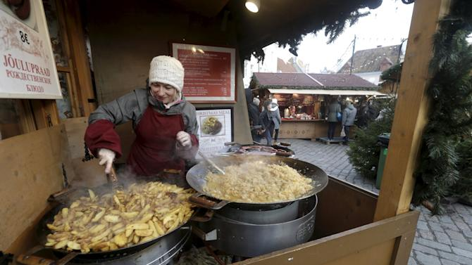 A food vendor cooks in her stall at a Christmas market in Tallinn