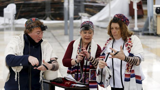 "Members of the activist group, ""Women of the Wall"", wear Jewish prayer shawls and tefillin during an event teaching people how to put on the tefillin, near the Western Wall in Jerusalem's Old City"