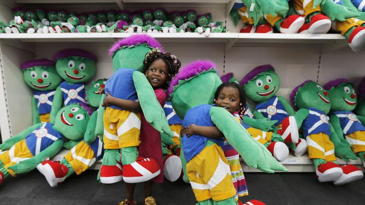 Grace and her sister Glorie Minga hold Clyde mascot dolls in the Glasgow 2014 Superstore at George Square in Glasgow, Scotland