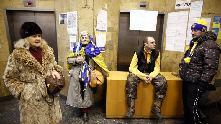 Pro-European integration protesters wait in front of entrance of improvised kitchen at Independence Square in Kiev