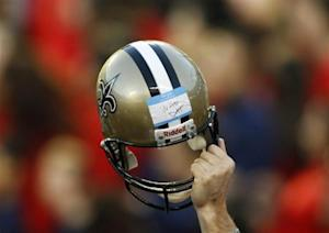 A member of the Saints staff holds up a helmet during the NFL's Super Bowl XLIV football game against the Indianapolis Colts in Miami