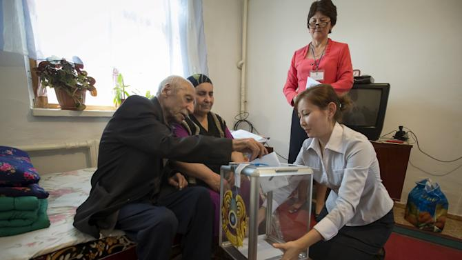 An elderly man casts a ballot in his home during a snap presidential election in the village of Tuzdybastau, Kazakhstan