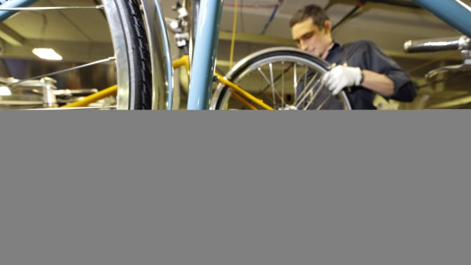 In a photo from April 10, 2013 in Detroit Alex Stchekine assembles a Shinola bicycle at the company's manufacturing facility. Detroit has a long history of making stuff _ cars, steel, even popcorn and is now home to a facility devoted to the production of wristwatches and bicycles. The frames are produced in Wisconsin and assembled in Detroit. (AP Photo/Carlos Osorio)