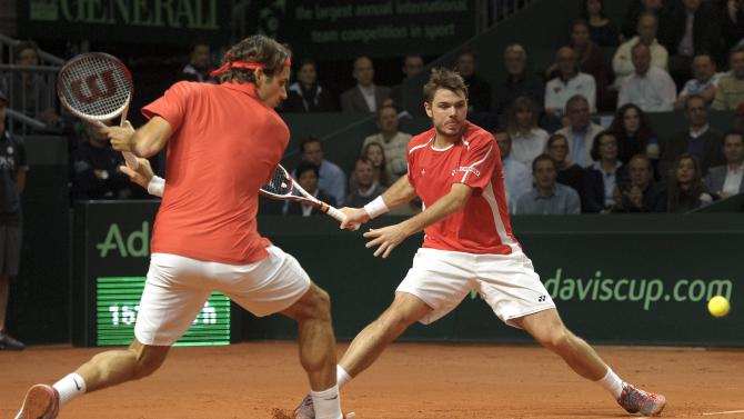 Swiss Davis Cup tennis player Stanislas Wawrinka, right, returns a ball next to his teammate Roger Federer to US Davis Cup tennis players Mardy Fish and Mike Bryan during the Davis Cup World Group first round double match between Switzerland and the US in the Forum Arena in Fribourg, Switzerland, Saturday, Feb. 11, 2012. (AP Photo/Keystone, Laurent Gillieron)