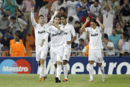 Real Madrid's Cristiano Ronaldo from Portugal, left, celebrates after scoring against Ajax during his group D Champions League soccer match at the Santiago Bernabeu stadium, in Madrid, Tuesday, Sept. 27, 2011. (AP Photo/Daniel Ochoa de Olza)
