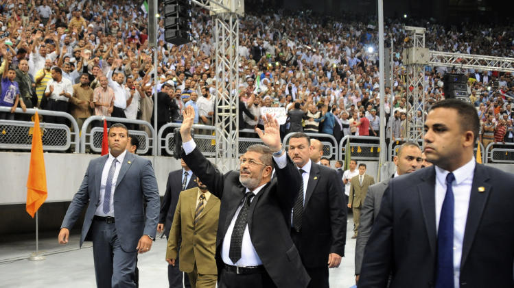 """In this image released by the Egyptian Presidency, Egyptian President Mohammed Morsi waves as he arrives at a rally called for by hardline Islamists loyal to the Egyptian president to show solidarity with the people of Syria, in a stadium in Cairo, Egypt, Sunday, June 15, 2013. Egypt's Islamist president announced Saturday that he was cutting off diplomatic relations with Syria and closing Damascus' embassy in Cairo, decisions made amid growing calls from hard-line Sunni clerics in Egypt and elsewhere to launch a """"holy war"""" against Syria's embattled regime. (AP Photo/Egyptian Presidency)"""
