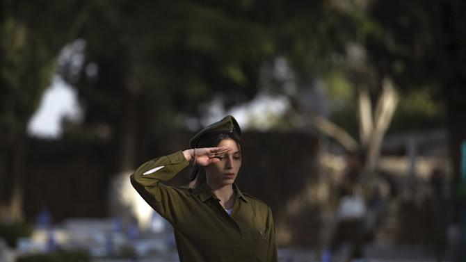 An Israeli soldier salutes next to graves of fallen soldiers during a ceremony at the Mount Herzl military cemetery in Jerusalem