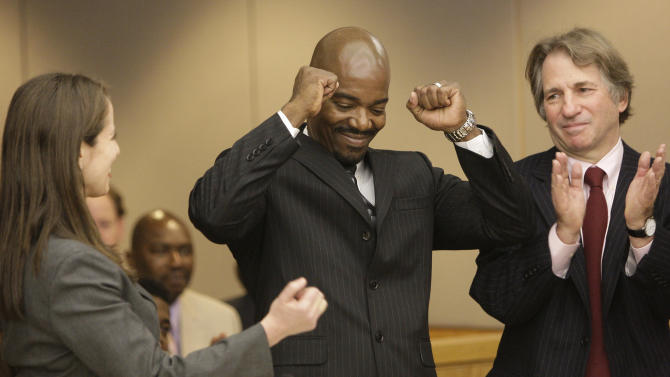**CORRECTS YEAR TO 2011**Cornelius Dupree Jr., center, raises his hands in celebration with his lawyer Nina Morrison, left, and attorney Barry Scheck in Dallas on Tuesday, Jan. 4, 2011. Dupree served 30 years for rape and robbery before being exonerated by DNA evidence. (AP Photo/Mike Fuentes)