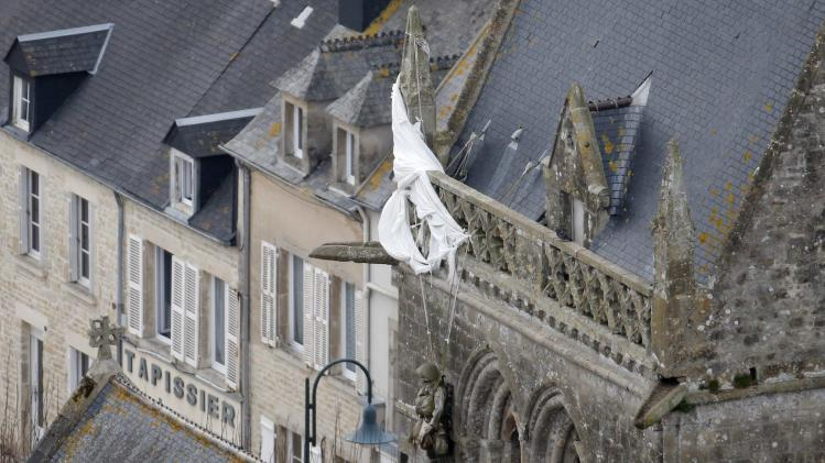 An aerial view shows a parachute with an effigy of Private Steele in his Airborne uniform hanging from the steeple of the Sainte-Mere-Eglise church in the French Normandy region