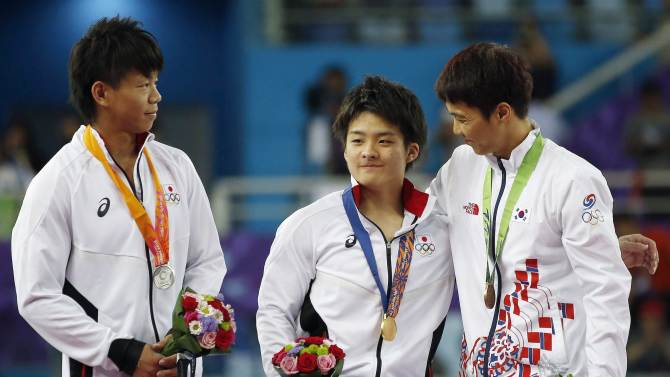 Gold medallist Japan's Kamoto talks with bronze medallist South Korea's Lee and silver medallist Japan's Yamamoto during the medal ceremony at the Namdong Gymnasium Club during the 17th Asian Games in Incheon