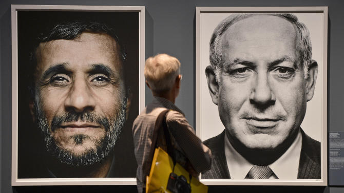 "FILE - In this Wednesday, Sept. 19, 2012 file photo, a visitor looks at portraits of Iran's President Mahmoud Ahmadinejad and Israel's Prime Minister Benjamin Netanyahu during the exhibition ""faces of power"" by Greek photo artist Platon Antoniou, shown at the Photokina 2012 in Cologne, Germany. Israeli Prime Minister Benjamin Netanyahu heads to the United Nations this week with a single item on his agenda: Iran. Netanyahu is convinced the Islamic Republic isn't taking American vows to block it from acquiring nuclear weapons seriously and that time is quickly running out to stop them. (AP Photo / Martin Meissner, File)"