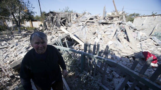 A woman observes damage at a destroyed home after shelling in the town of Donetsk, eastern Ukraine, Monday, Sept. 29, 2014. Eastern Ukraine has suffered the worst violence in more than a week as fighting between pro-Russian rebels and government troops in the region killed at least 12 people and wounded over 30, officials said Monday. (AP Photo/Darko Vojinovic)