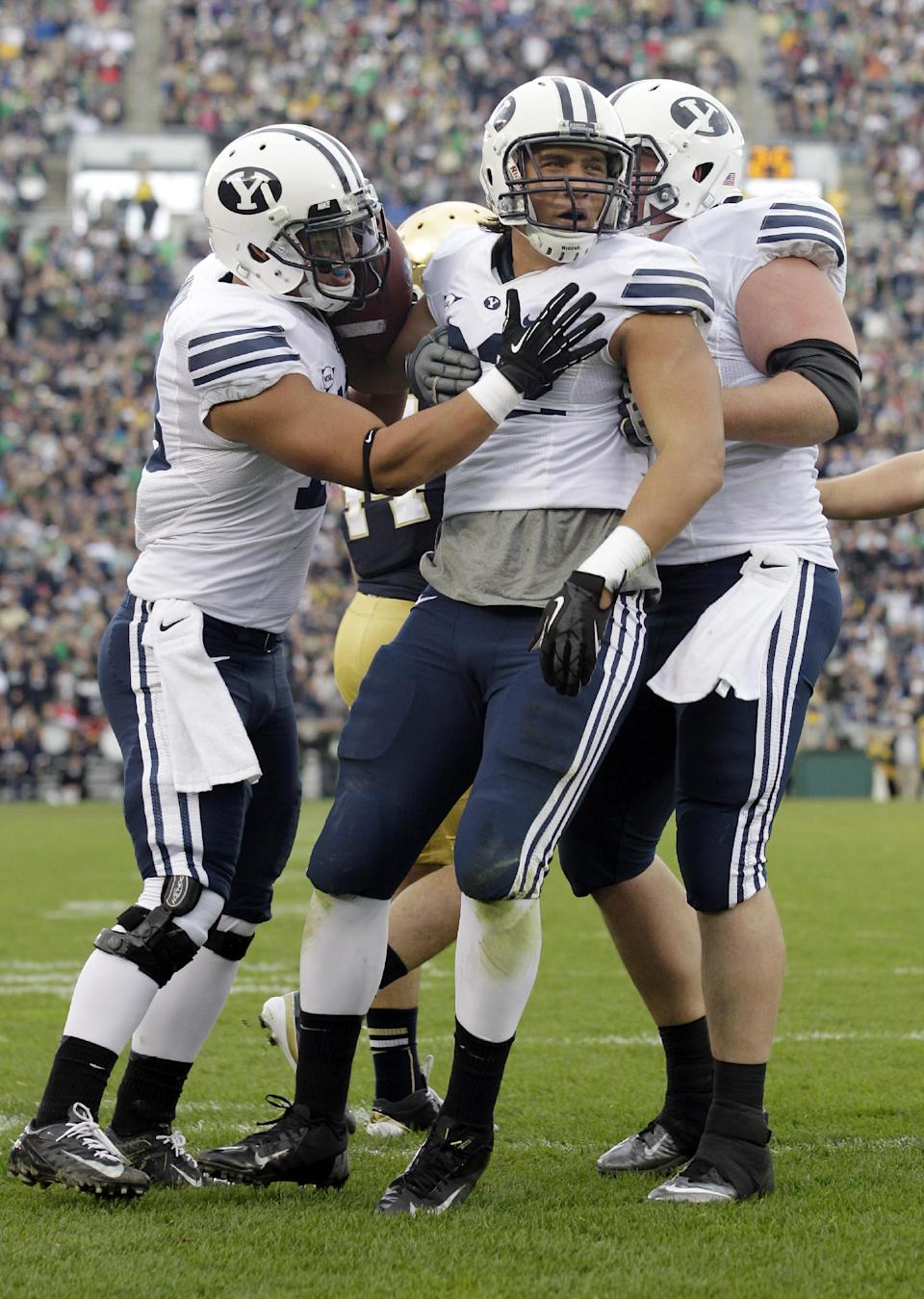 Brigham Young tight end Kaneakua Friel, center, celebrates a touchdown with tight end Richard Wilson, left, and offensive linesman Braden Hansen during the first half of an NCAA college football game against Notre Dame in South Bend, Ind., Saturday, Oct. 20, 2012. (AP Photo/Michael Conroy)