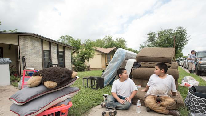 Kino Rodriguez, 8, left, and Israel Rodriguez, 7, sit outside their families flood-damaged home and discuss their experiences with the flooding from the night before on Sunday May 24, 2015, in San Marcos, Texas. Record rainfall was wreaking havoc across a swath of the U.S. Midwest on Sunday, causing flash floods in normally dry riverbeds, spawning tornadoes and forcing at least 2,000 people to flee. (Erika Rich/Austin American-Statesman via AP)  AUSTIN CHRONICLE OUT, COMMUNITY IMPACT OUT, INTERNET AND TV MUST CREDIT PHOTOGRAPHER AND STATESMAN.COM, MAGS OUT